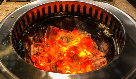 Glowing and flaming hot natural wood charcoal in BBQ grill stove background.