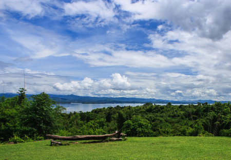 beautiful garden in front of blue Srinakarin dam with clear blue sky, Kanchanaburi province, Thailand