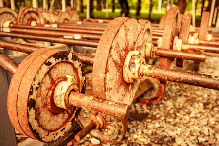 operational: vintage view of rusty old operational barbells mounted on the stand in public park