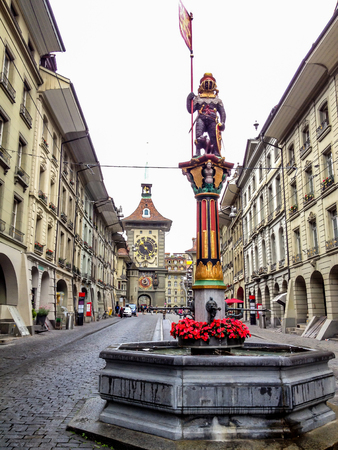 Beautiful City Street View of the colorful medieval Zahringen statue on top of elaborate fountain in Bern, Switzerland. The fountain is attributed to Hans Gieng in 16th century.