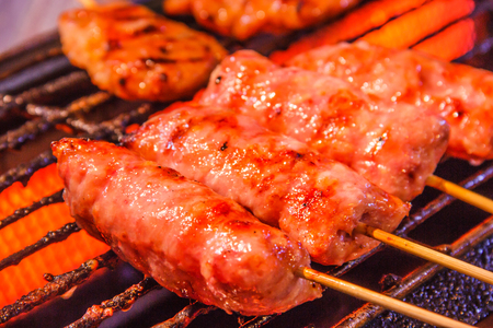 Traditional Thai Isaan Sausage roasted on the charcoal grill background. Asian, Thai styled street food appetizer.