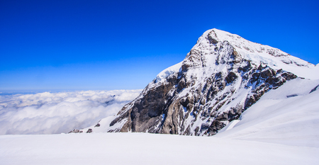 View of Summit of Mount Jungfrau (Jungfraujoch) with cloud and blue sky background, Jungfraujoch Railway Station, Bernese Oberland region, Switzerland, Europe.