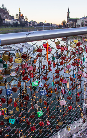 Old tradition of sealing a couples initial names inscribed padlock with the popular bridge and tossing the key into the river to symbolize their eternal love. Makartsteg footbridge or Makartsteg Brucke, Salzburg, Austria, Europe. Foto de archivo