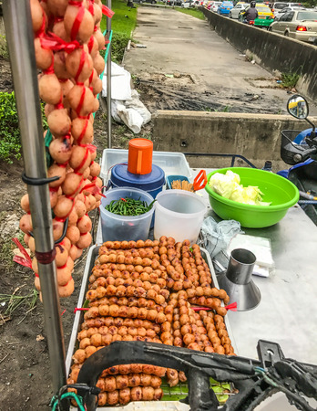 Traditional Thai charcoal roasted Isaan Sausage, on the stall with road traffic background. Asian, Thai styled street food appetizer.