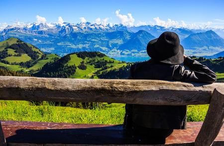Aziatische vrouw op het bankschatten mooi toneelpanorama van majestueuze Zwitserse alpen dat Rigi Kulm, de koningin van bergen omringt, bij Rigi Kulm Post, Luzerne, Zwitserland, Europa.