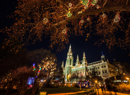 Colorful Light Illuminated Night Christmas Market with crowd motion blurred at the Vienna City Hall at Rathausplatz, Austria, Europe.
