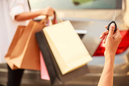Female Ladies carrying Colorful Shopping Bags in the parking lots Concept. Lady hand using remote control to send signal to unlock car doors and trunk. Stock Photo