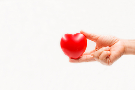 Heart shape in the helping hand on white background. Heart illness, disease protection, proactive checkup, mind diagnosis, sickness prevention, healthcare concept Banco de Imagens