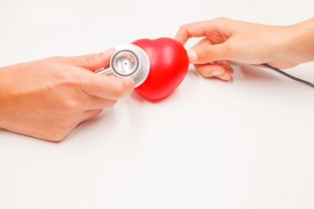 Hands with stethoscope and charging cable to check and cure heart on white background. Heart disease protection, proactive checkup, diagnosis, sickness prevention, healthcare examination tool concept.