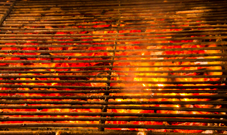 Glowing and flaming hot natural wood charcoal in street food BBQ grill stove background. Stock Photo