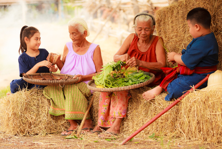 Traditional Asian Thai rural daily life, grandchildren in cultural costumes help their seniors preparing local food ingredients for the meal. Diversity in age, outdoor setting.