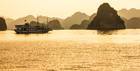 Ha Long bay islands, tourist boats and seascape in the evening with golden light reflection on water, Ha Long, Vietnam. Stock Photo