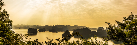Panorama of Ha Long bay islands, tourist boat and seascape in the evening with golden sunlight beam reflection on water, Ha Long, Vietnam.