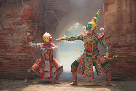 Hanuman (monkey god) fighting Thotsakan (giant) in Khon or Traditional Thai Pantomime as a cultural dancing arts performance in mask dressed based on the character in Ramakien or Ramayana Literature. Stock Photo