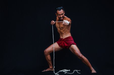 Handsome Muscular Man displays ancient Asian traditional martial arts, Thai Boxing or Muay Thai