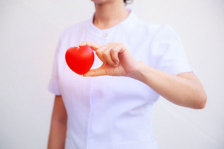Selective focus of red smiling heart held by female nurse's hand, representing giving effort high quality service mind to patient. Professional, Specialist in uniform isolated white background