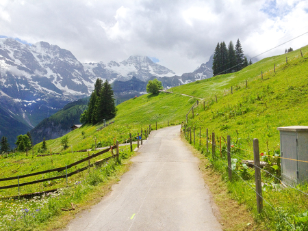 Spectacular panoramic view from Murren-Gimmelwald walking trail with Eiger, Monch and Jungfrau Swiss alps mountain peaks in background, Switzerland, Europe. Family Activity from Lauterbrunnen station. 스톡 콘텐츠