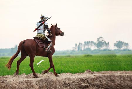 Guerrero tailandés asiático en traje de armadura tradicional a caballo en el fondo de la granja rural. Concepto de traje de guerra retro vintage. Foto de archivo
