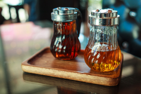 Glass bottles in wooden tray on table, containing hazelnut and caramel liquid syrups for flavoring coffee, drinks and sweet desserts