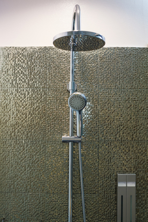 Luxury modern stainless steel ceiling rain shower, Shower head faucet and holder in bathroom on golden decorating tiles wall background. Interior Architecture Bathroom Decoration Design