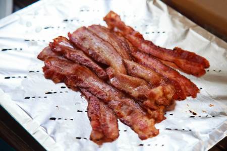 hot delicious freshly cooked grilled pork bacon ready to eat on aluminum foil. Healthy and hearty oil fried meat rich with fat and protein, international american buffet breakfast food background. Stock Photo