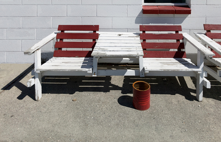 maroon and white color painted wooden outdoor summer bench chair against white brick concrete block wall background and red bucket as an cigaret ashtray. Smoking designated and sitting area concept