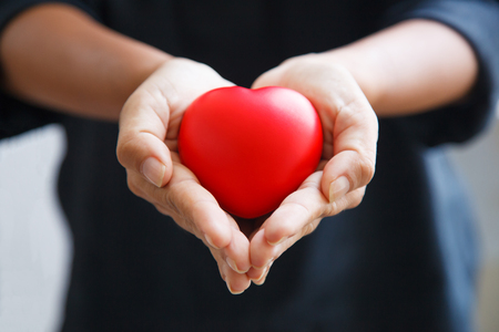 red heart held by female's both hands, represent helping hands, caring, love, sympathy, condolence, customer relationship, patient assistance, life moment, psychological support, service mind concept Reklamní fotografie