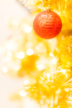 Glittering Bauble with Glowing Sparkling Gold defocused Light (bokeh) Illumination background with decorated Christmas Tree. Special Holidays, Festival design decoration, New Year Celebration, Party.