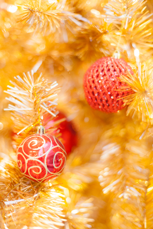 Glittering Baubles with Glowing Sparkling Gold defocused Light (bokeh) Illumination background with decorated Christmas Tree. Special Holidays, Festival design decoration, New Year Celebration, Party.