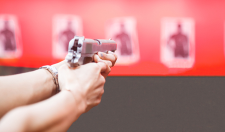 Woman Both Hands holding magnum gun, index finger on trigger, aiming ready to shoot on targets on red wall background. Sport, Recreation, Weapon, Firearm Practice, Concentration, Precision concept