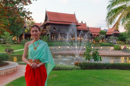 Young Beautiful Thai Asian woman dressing in vintage retro Traditional Thai costume in wait to welcome guest. Thailand Cultural and Traditional Tourism, Asian Rural Daily Life, Thai Heritage concept