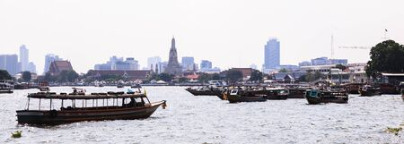 Thai riverside naval commuter traffic in Chao Phraya River with Wat Arun (Temple of Dawn) background, Bangkok, Thailand. Thailand Tourist Attraction, Traditional Travel Asia and River Cruise concept.