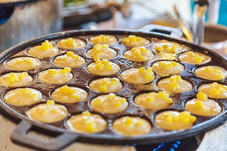 Khanom Khrok (coconut rice pancake), Traditional Thai Pudding Pancake Dessert, prepared by mixing rice flour, sugar, and coconut milk to form dough cooked in heating mantle (hot indented frying pan)