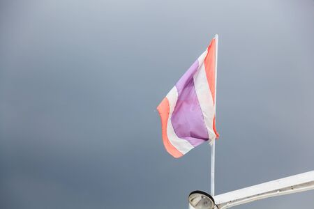 Sign and Symbol. Thai National Tricolor Flag (5 horizontal stripes in colors red, white and blue at center) on boat on cloudy sky background. Red is for nation, White for religion and blue for king. 写真素材