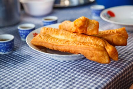 Youtiao (Chinese fried churro, Chinese cruller, Chinese oil stick, Chinese doughnut, fried breadstick), long golden brown deep fried dough strip, eaten at breakfast with rice congee, tea or sweet milk