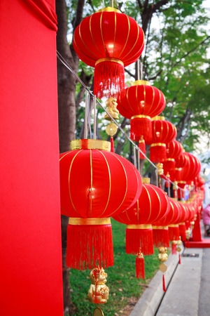Traditional Chinese Red Nylon Outdoor Vintage Hanging Pendant Light Lanterns with golden tassels decoration adorning street lights, buildings and shops for Chinese New Year Festival Season Celebration Stock Photo