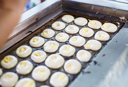 Vendor Cooking Khanom Kai (Chinese Egg Cake), traditional Thai baked sweet dessert mini castella cake made of starch, flour, egg, sugar. Thai Food, Bakery, Snack, Cuisine, Sponge Cake, Gourmet concept