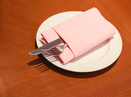 pastel cloth napkin (serviette) folding with cutlery (knife, fork, silverware) in white plate prepared on the wooden table, ready for customer to use. Hotel restaurant food catering service concept