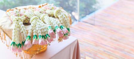 Fresh flower garland in metal tray on reception desk background. Decorative Ornamental Flower, Nature, Valentine Day, Home Decoration, Bridal Wedding Reception, Floral Arrangement and Interior concept