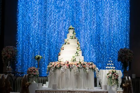Wedding Cake on the table decorated by beautiful flowers at the stage with beautiful glittering blue light bokeh backdrop in wedding night ceremony. Wedding Ceremony tools and decorations concept. Banco de Imagens