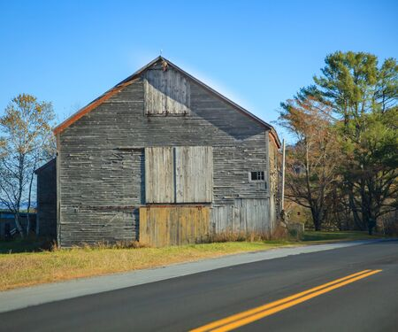 Old Rural Remote Aged Vintage Wooden Warehouse Building along the Street. Barn, Farmhouse, Garage, Storage, Granary, Logistics, Transportation, Industry, and Agriculture concept Stock fotó