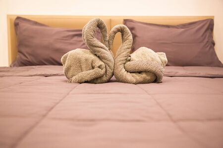 Romantic Bedroom Interior, Kissing Swan Origami Towels decoration on the hotel room bed for newlywed couple. Wedding, Valentine, Anniversary, Honeymoon, Craft, Accommodation, Love and Symbol concept