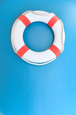 Bright Life Buoy in Blue background. Personal life support flotation safety device for swimmers, passengers or marine personnel working in area exposed to water. Drowning Protection Equipment concept.