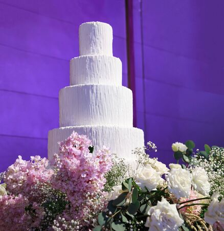 Wedding Cake with beautiful flowers decoration at the stage in front of purple light backdrop in wedding reception night ceremony. Food Catering and Venue for Bridal Wedding and Marriage concept