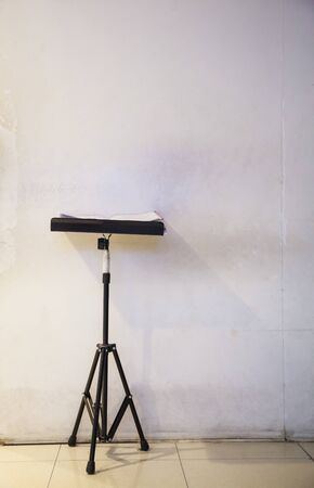 black metal tripod stand provides platform to security daily log books for recording reports in front of temporary white wooden wall background in renovating site. Safety Discipline and Tools concept