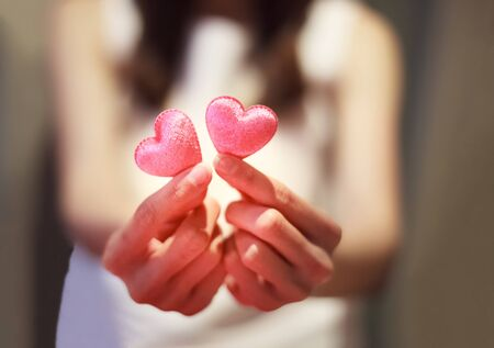 pink hearts held by female's both hands, represent helping hand, dating, caring, love, sympathy, condolence, romance, relationship, patient assistance, psychological support and Valentine day concept