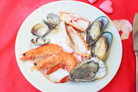 Seafood Platter Lover: fresh sweet shrimps, raw snow crab meat, mussels, oyster, clams and enamel venus shells served in white plate on dining table. Dish, Nutrition, Food, Meal and Cuisine concept Foto de archivo