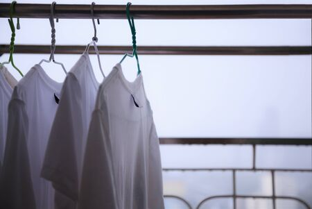 White T Shirts hung on Cloth hangers on Cloth Line at the balcony of residential building in a rainy day with blurry city view background, cannot dry clothes on bad day. City Life, Living on High Rise