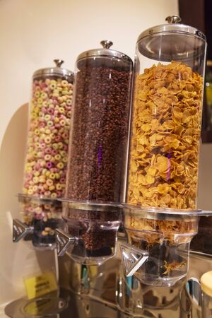 Selective Focused Variety of Breakfast Cereals Morning Meal; Crisp Dark Chocolate, Corn Flakes and Fruit Loops in Cereal Glass Jar Dispensers. Nutrition, Food Storage and Hotel Food Catering concept.