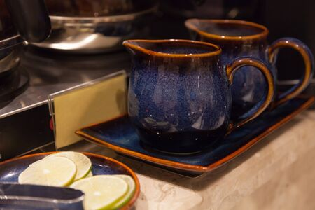 Hand Crafted Vintage Asian Tea Drinking Jugs placed in earthenware tray on table floor, ready to use. Liquid serving containers used in Food and Drink Catering Service Industry, Utensils concept.